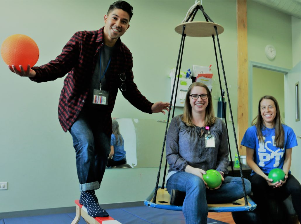 Physical Therapists pose on swing