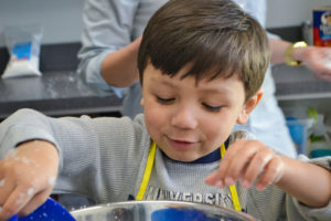 Blue Bird Day banner: child stirring bowl and smiling.